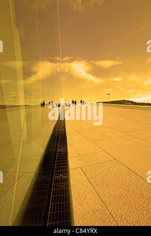 La riflessione in un edificio di vetro al tramonto Foto Stock