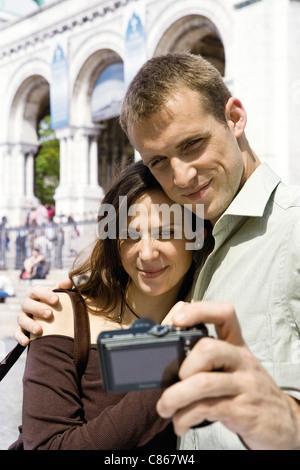 Uomo di fotografare se stesso e la sua fidanzata con fotocamera digitale Foto Stock