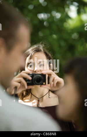 Fotografare la donna giovane con fotocamera digitale, al di sopra della spalla Foto Stock