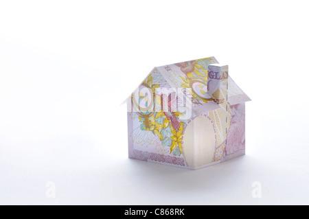 Modello di casa piegato con British pound banconota Foto Stock