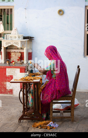 Donna indiana in sari di Rajasthani lavora a casa utilizzando la macchina da cucire in Nimaj village, Rajasthan, Foto Stock