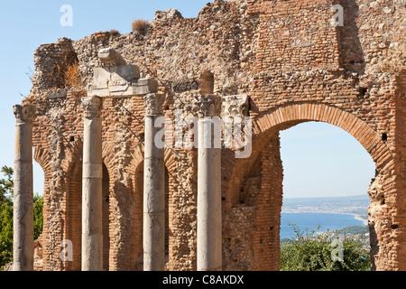 Le colonne e la parete interna del Teatro Greco e la vista del golfo di Giardini Naxos, Taormina, Sicilia, Italia