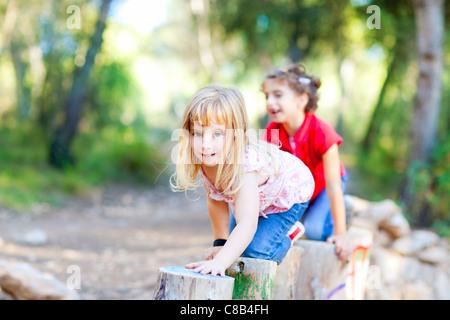 Kid ragazze giocando sui trunk ginocchio a piedi nella natura della foresta Foto Stock