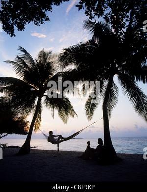 Giovane relax su una spiaggia al tramonto, Maldive, Oceano Indiano Foto Stock