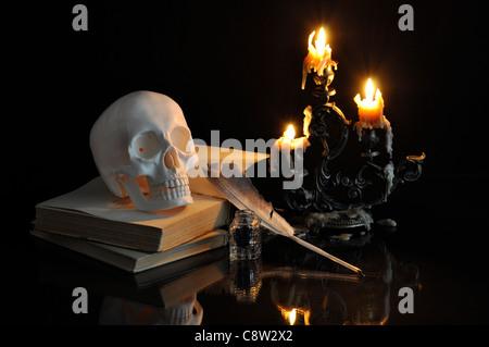 Natura morta con cranio, libri e candele su sfondo nero Foto Stock