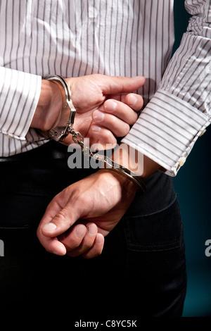 Un collare bianco penale in manette su sfondo blu. Foto Stock