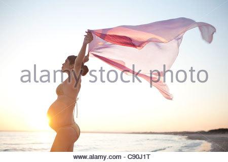 Donna incinta camminando sulla spiaggia Foto Stock