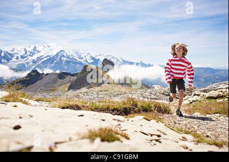 Ragazzo in esecuzione nel paesaggio roccioso Foto Stock