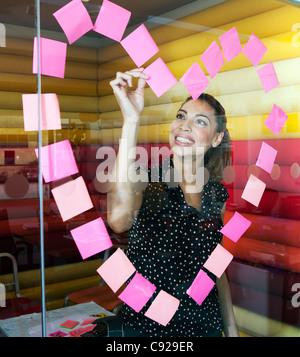 Imprenditrici rendendo cuore con note Foto Stock