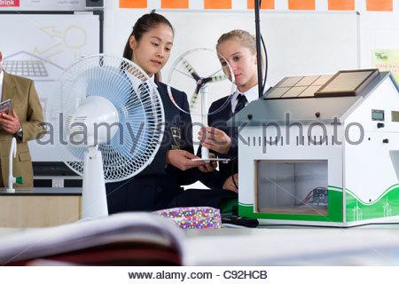 Studentesse in uniformi di scuola azienda turbina eolica modello nella classe di scienze Foto Stock