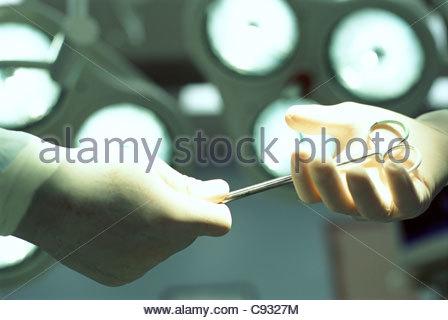Close up di chirurghi in guanti di gomma con le forbici Foto Stock