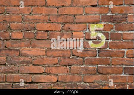 Il numero 5 dipinta su un muro di mattoni nel Pearl District di Portland, Oregon.