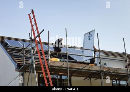 Regno Unito, Gran Bretagna. Operai il montaggio di nuovi pannelli solari per un tetto di casa per il feed-in regime Foto Stock