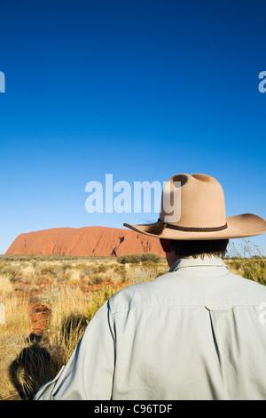 Un outback guida guardando verso Uluru (Ayers Rock). Uluru-Kata Tjuta National Park, il Territorio del Nord, l'Australia