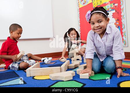I bambini sul pavimento con la costruzione di blocchi Foto Stock
