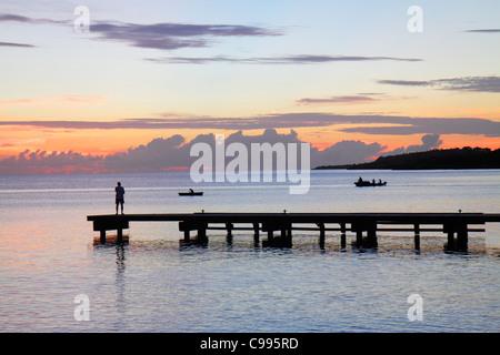 Curaçao Antille olandesi Dutch Piscadera Bay Mar dei Caraibi pier man standing costa in barca al tramonto rosa crepuscolo Foto Stock