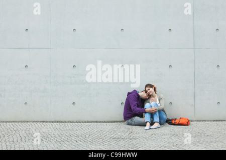 Germania, Berlino, giovane seduto di fronte a grande parete sul marciapiede