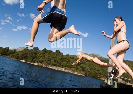 Un gruppo salta fuori da un molo in un lago. Il lago di Rosebery, Tullah, Tasmania, Australia Foto Stock