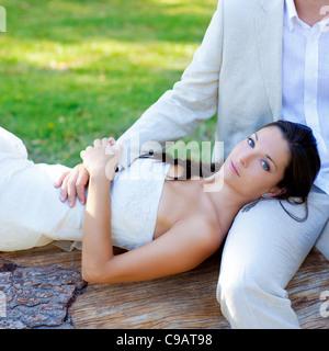 Donna sdraiata sul marito della gamba in un parco tronco appena sposato Foto Stock