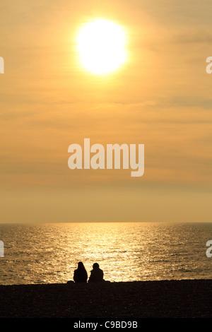 Stagliano giovane seduto sulla spiaggia di Brighton la visione di Sun inferiore in autunno tramonto Foto Stock