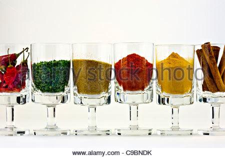 Selezione di spezie in bicchieri contro uno sfondo bianco Foto Stock