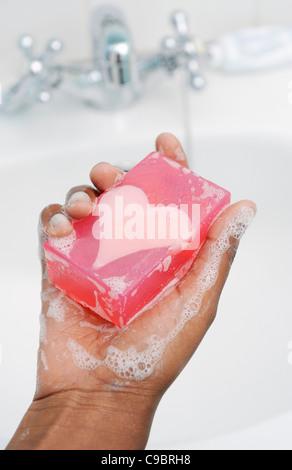 La mano della ragazza adolescente tenendo premuto barra di sapone a forma di cuore, Cape Town, Provincia del Capo Occidentale, Sud Africa
