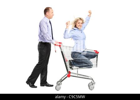 Persona spingendo una donna felice in un carrello della spesa Foto Stock