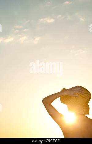 Donna all'aperto stagliano contro il sole di setting Foto Stock