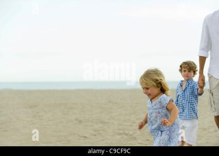 Bambina per divertirsi in spiaggia con la famiglia Foto Stock