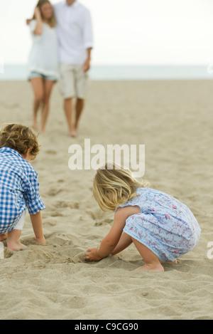 Bambini che giocano nella sabbia in spiaggia Foto Stock