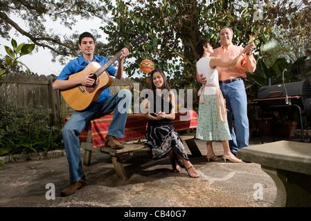 Una famiglia Mexican-American la riproduzione di musica e danza nel cortile di casa loro Foto Stock