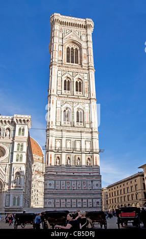 I turisti e i locali al di fuori il Campanile di Giotto accanto al Duomo di Firenze, Toscana, Italia, con cavalli Foto Stock
