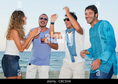Gli amici di ridere insieme sulla spiaggia