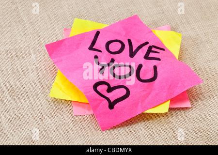 Ufficio concetto romance - amore è il testo scritto a mano di colore rosso su una nota adesiva Foto Stock