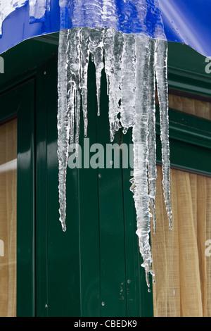 Fusione di ghiaccioli e gocce di acqua da un edificio in metallo con tetto trapulin Foto Stock