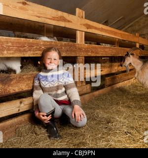 Ragazza all'interno di un fienile con capre, allevamento di capre, Islanda Foto Stock