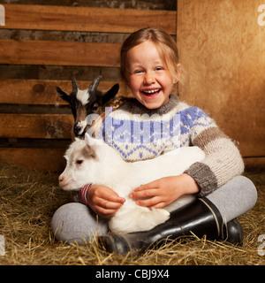 Ragazza holidng capretto, allevamento di capre Islanda Foto Stock