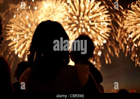 Silhouette di madre e figlia a guardare i fuochi d'artificio
