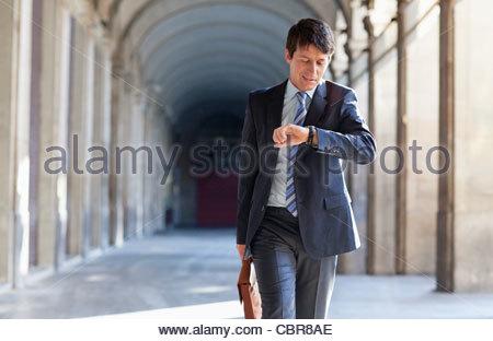 Imprenditore controllando il tempo all'aperto Foto Stock