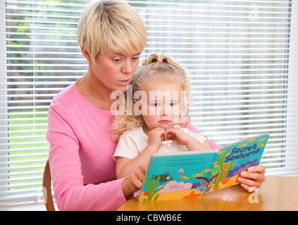 Madre insegnare ai giovani la figlia per la lettura di un libro Foto Stock