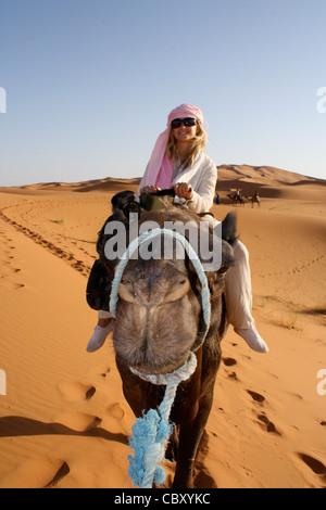 Una donna a dorso di un cammello in Erg Chebbi, Sahara, Marocco Foto Stock