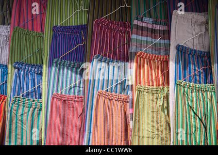 Una varietà di coloratissimi pantaloni di panno appeso in un display al mercato di Otavalo, Ecuador. Foto Stock