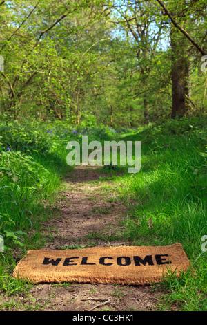 Concetto foto di un benvenuto zerbino su un sentiero di bosco durante la primavera in formato verticale. Foto Stock