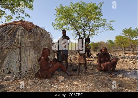 Himba gli abitanti di un villaggio vicino al fiume Kunene, il confine tra Angola e Namibia. Kaokoland, Namibia settentrionale. Foto Stock