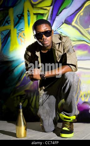 Giovani afro-americane uomo seduto davanti di colorati graffiti wall Foto Stock