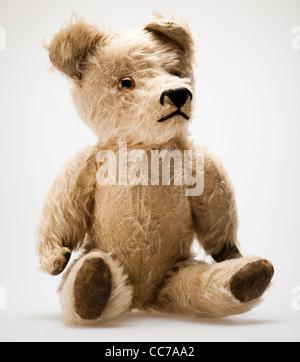 Un travagliato threadbare tradizionale vecchio childs giocattolo orsacchiotto Foto Stock