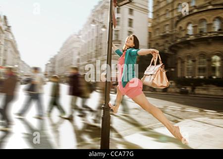 Metà donna adulta in abito rosa saltando attraverso le strade della città Foto Stock
