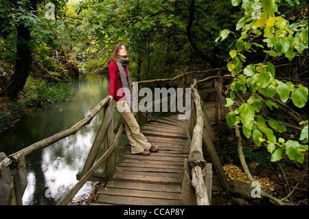 Bella giovane donna contemplando il cielo circondato da una lussureggiante vegetazione verde appoggiato su di un Foto Stock