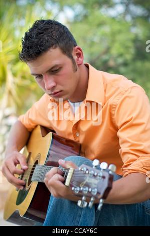 Giovane uomo a suonare la chitarra Foto Stock