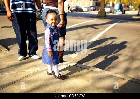 Una bambina cammina a casa con la sua famiglia dopo che hanno votato per Barack Obama sul lato sud di Chicago il Foto Stock